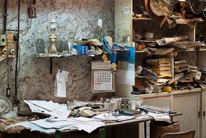 dirty office with books and papers messily stacked on top of desk