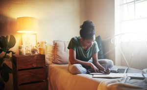 student studying in a bedroom room by herself